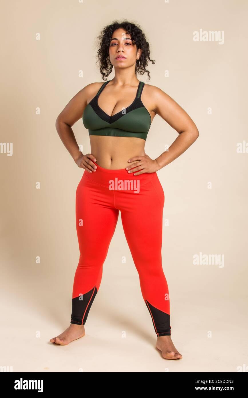 Mujer bastante grande llevando ropa deportiva posando en el estudio - hermosa chica aceptando la imperfección corporal, disparos de belleza en el estudio - conceptos sobre el cuerpo a Foto de stock