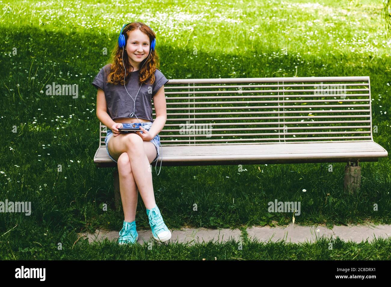Chica sonriente escuchando música a través de los auriculares mientras se sienta en el banco en el parque Foto de stock