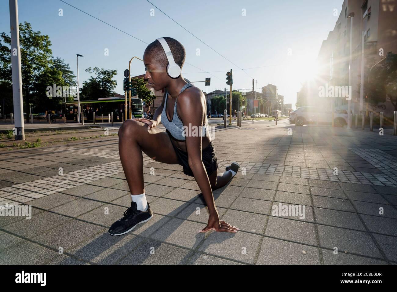 Mujer con cabeza afeitada escuchando música a través de los auriculares mientras se estira piernas en la calle en la ciudad Foto de stock