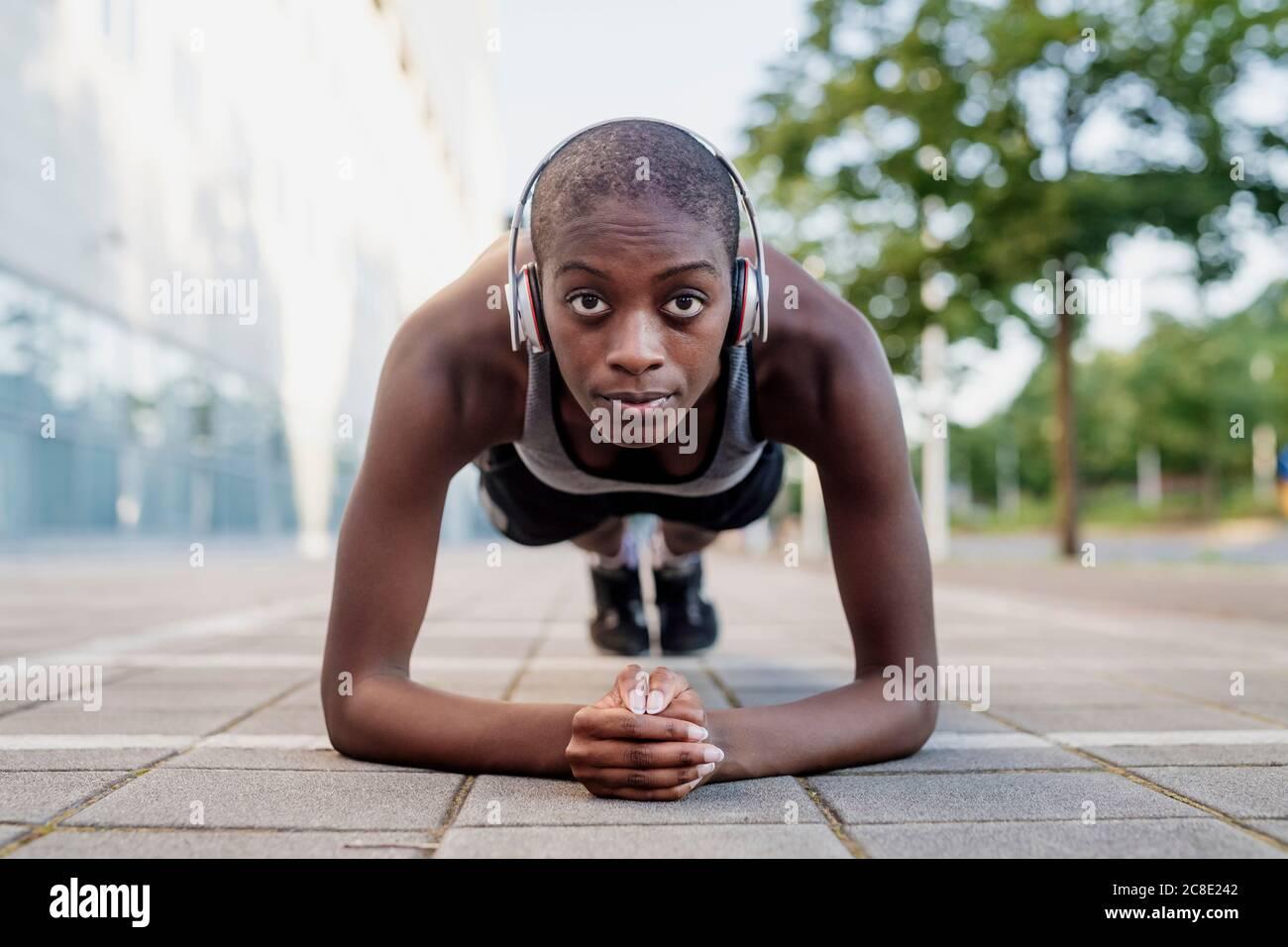 Mujer segura con cabeza afeitada escuchando música mientras hace tablones en el sendero Foto de stock