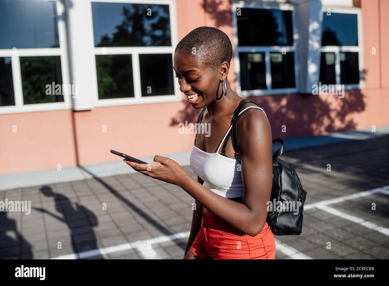 Alegre mujer joven con cabeza afeitada usando el teléfono inteligente mientras caminar en la acera de la ciudad Foto de stock