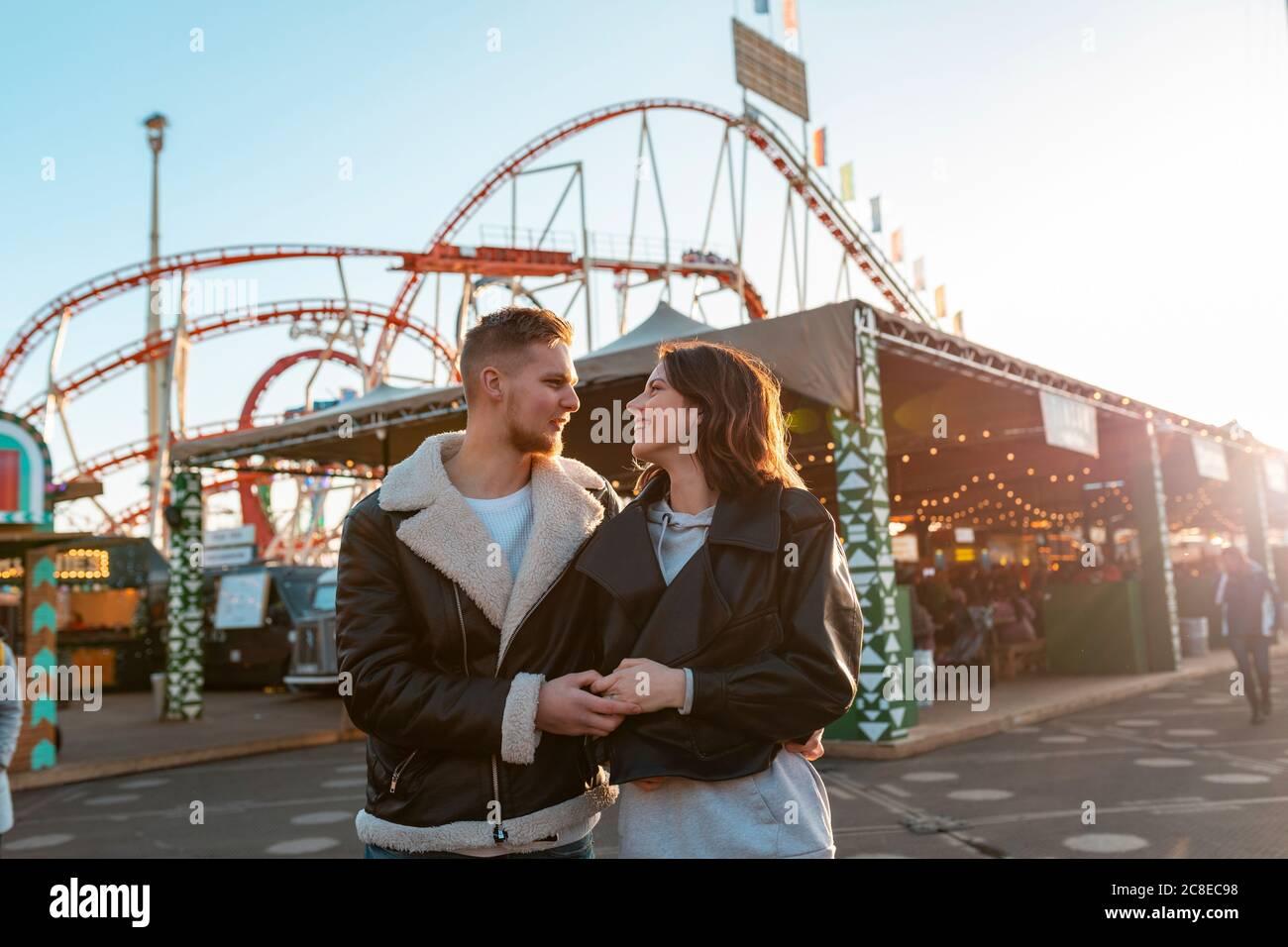 Pareja joven romántica con las manos mientras está de pie en el parque de atracciones durante la puesta de sol Foto de stock