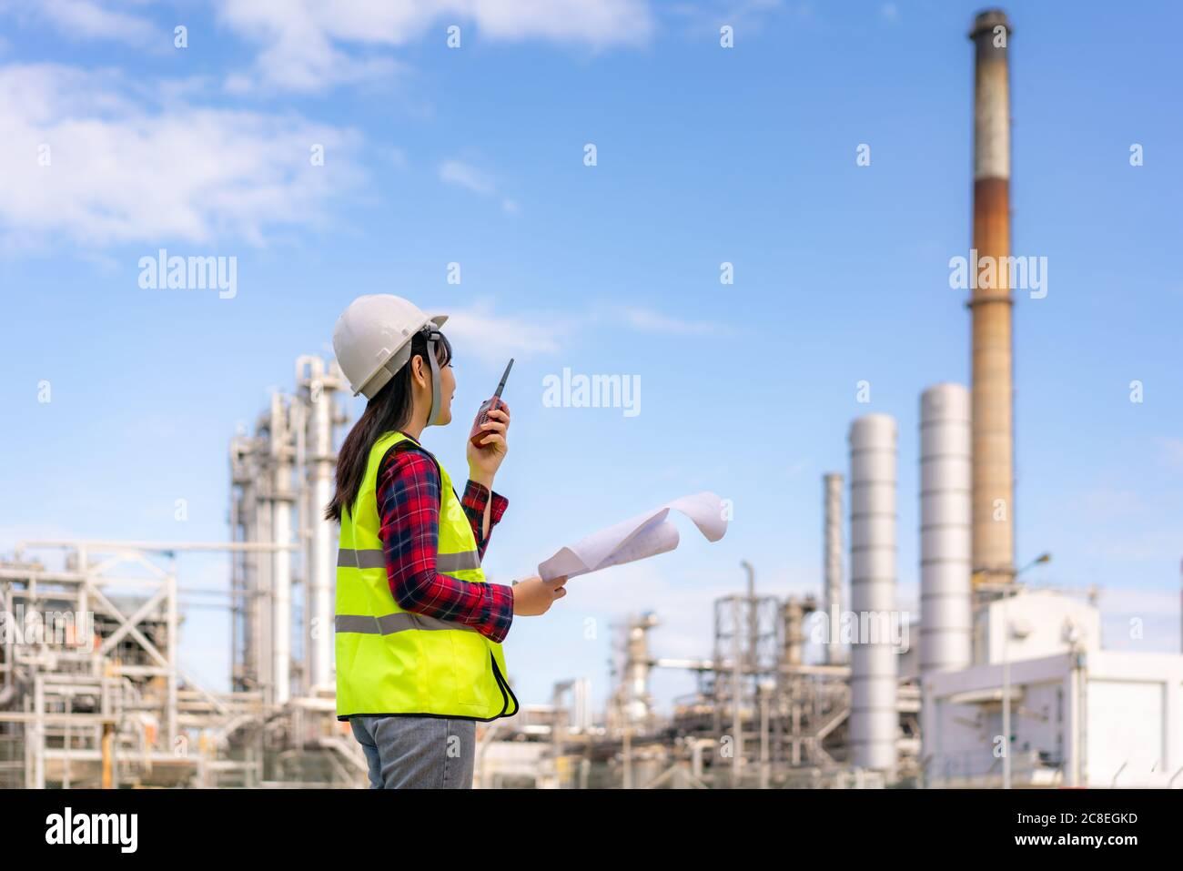 Mujer asiática técnico Ingeniero industrial usando walkie-talkie y sosteniendo bluprint trabajando en refinería de petróleo para la inspección de la obra en ingeniero civil Foto de stock