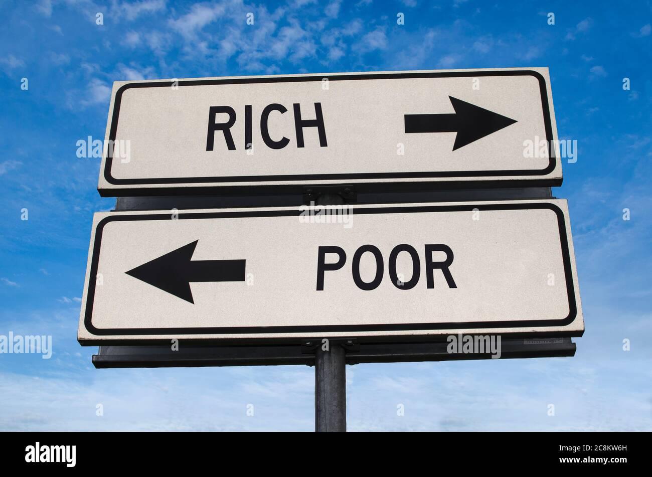 Señal de carretera rica y pobre. Dos señales de calle blancas con flecha en el poste de metal con palabra. Carretera direccional. Señal de cruce de carreteras, dos flechas. Cielo azul Foto de stock