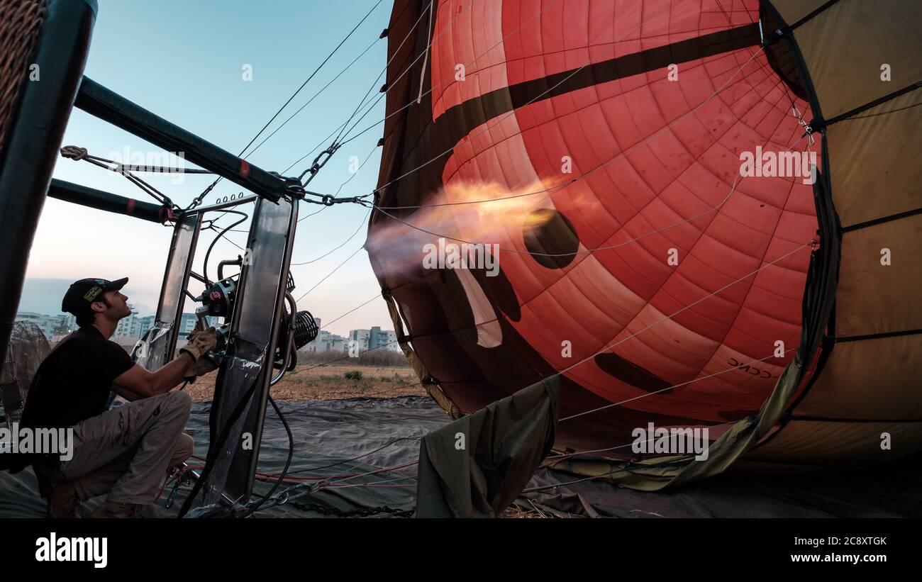 El piloto está calentando los quemadores de un globo inflable de aire caliente, minutos antes de despegar, Afula, Israel. Foto de stock
