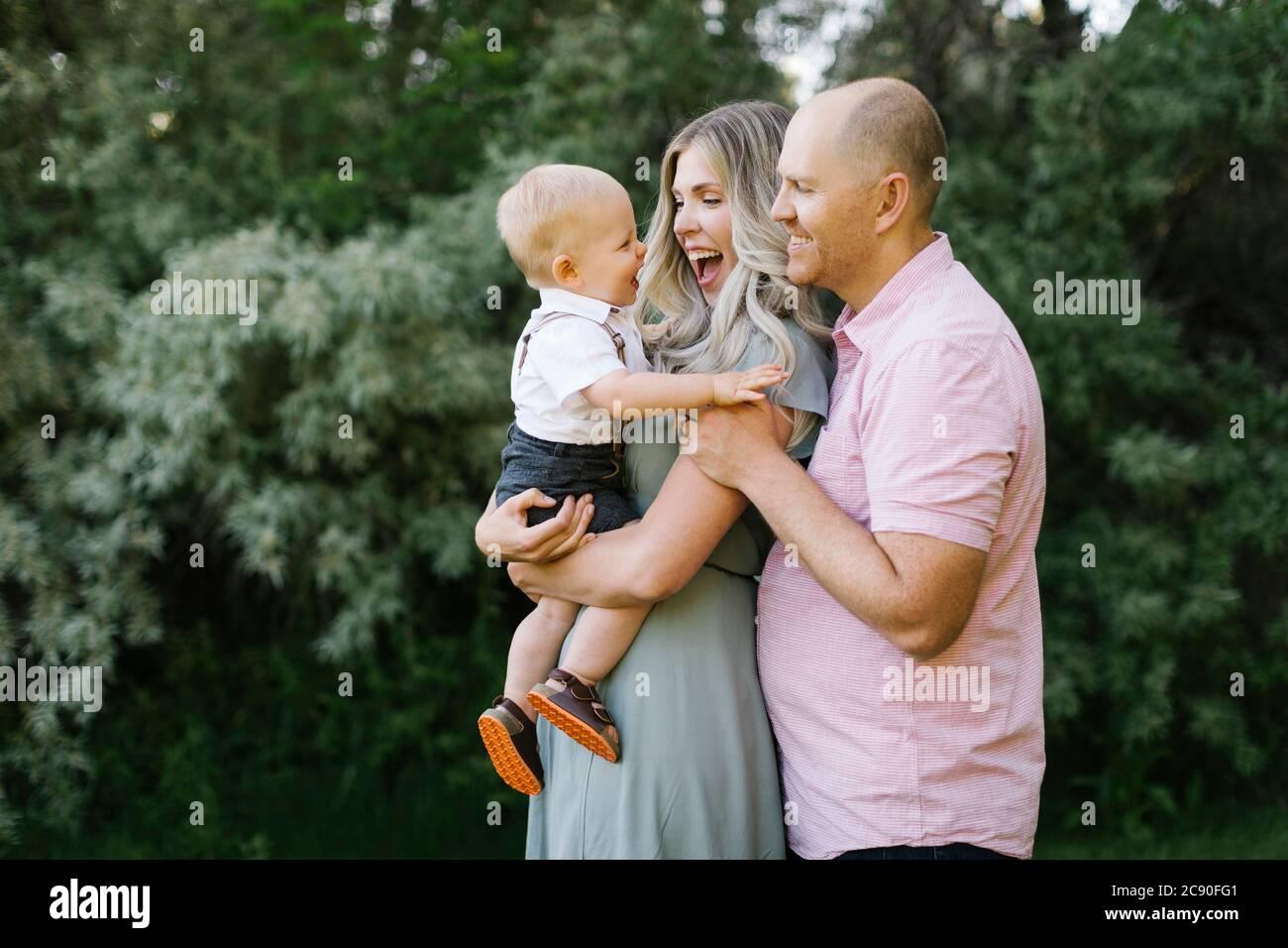 Padres abrazando con el bebé hijo al aire libre Foto de stock