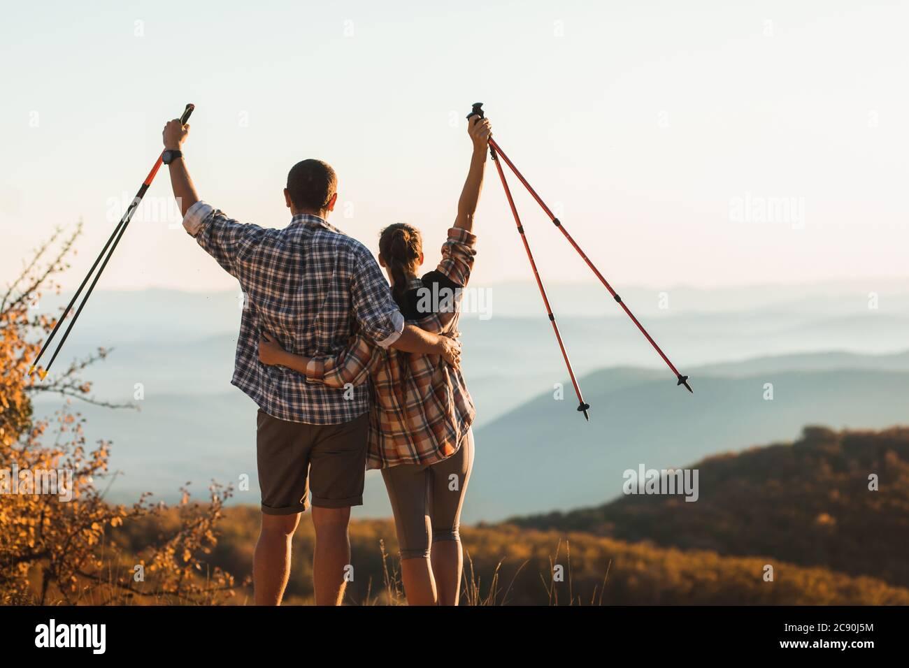 Pareja feliz de subir la cima de la montaña y mantener palos de senderismo. Marcha nórdica al aire libre, vista desde atrás. Viaje estilo de vida. Logro de la meta del éxito. Foto de stock