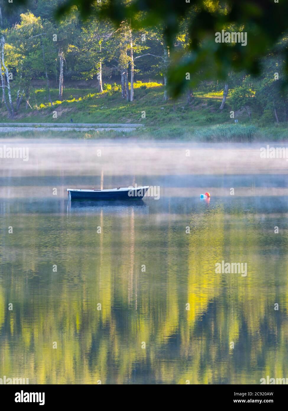 Lonesome barco en el lago Bajer en Fuzine Croacia Europa niebla vapor flotar flotar casi la superficie del agua Foto de stock