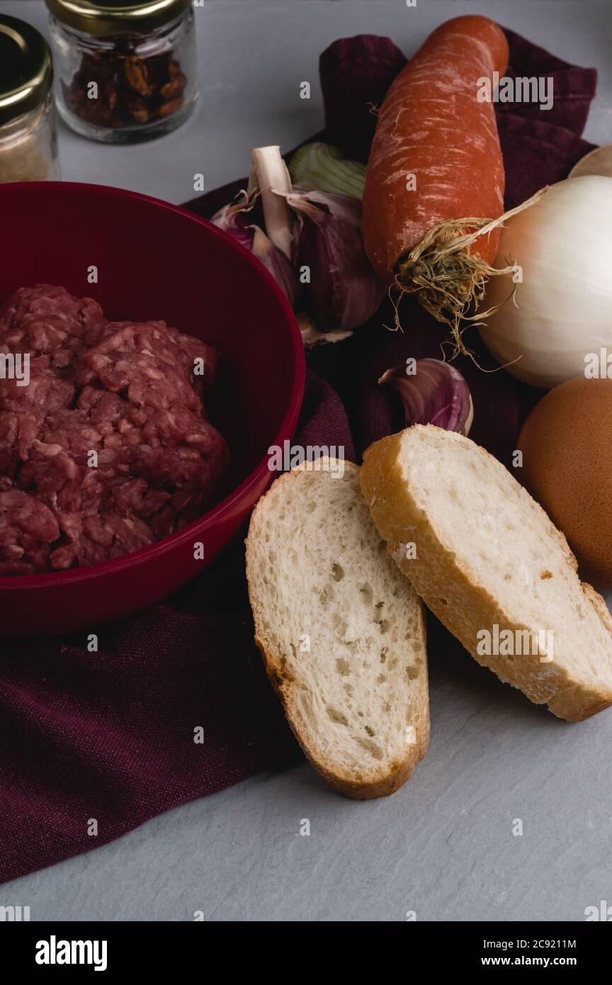 Verticcal primer plano de ingredientes para preparar albóndigas en un mesa de cocina blanca Foto de stock