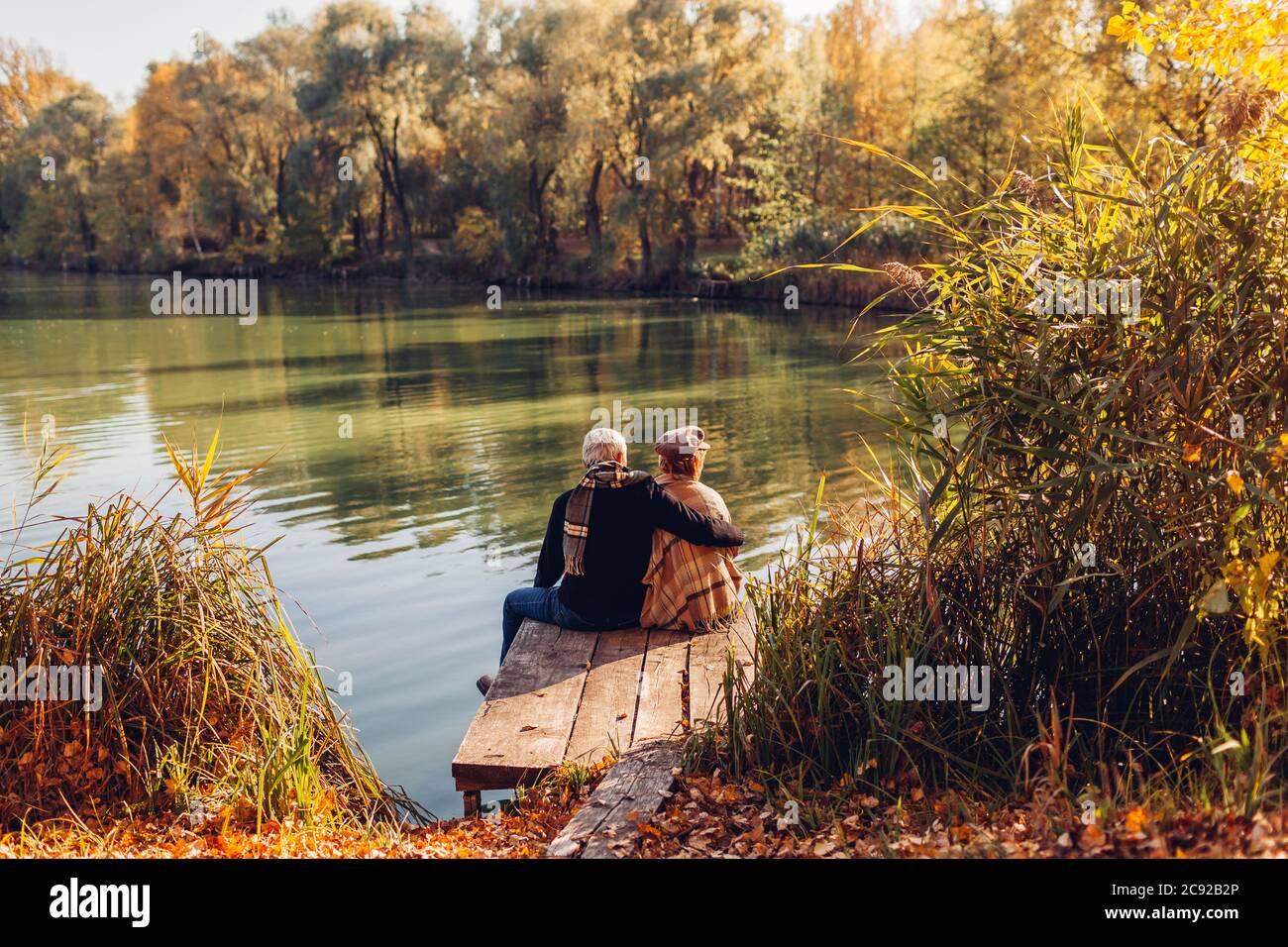 Pareja de la familia mayor relajándose en el lago de otoño. Hombre y mujer disfrutando de la naturaleza y abrazando sentado en el muelle Foto de stock