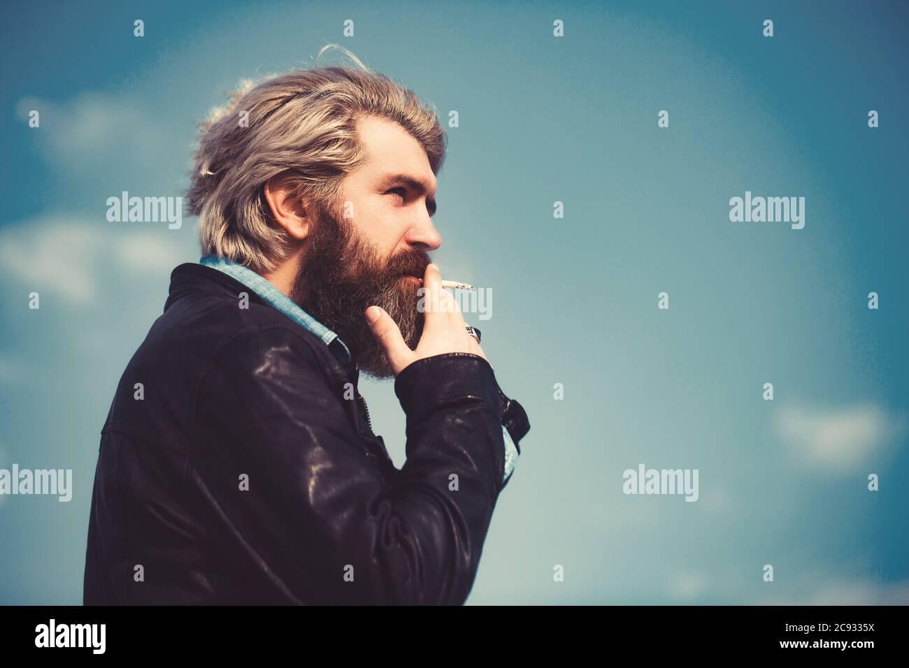 Cara de un hombre de mediana edad fumando un cigarrillo y mirando pensativo. Contra un cielo azul. Foto de stock