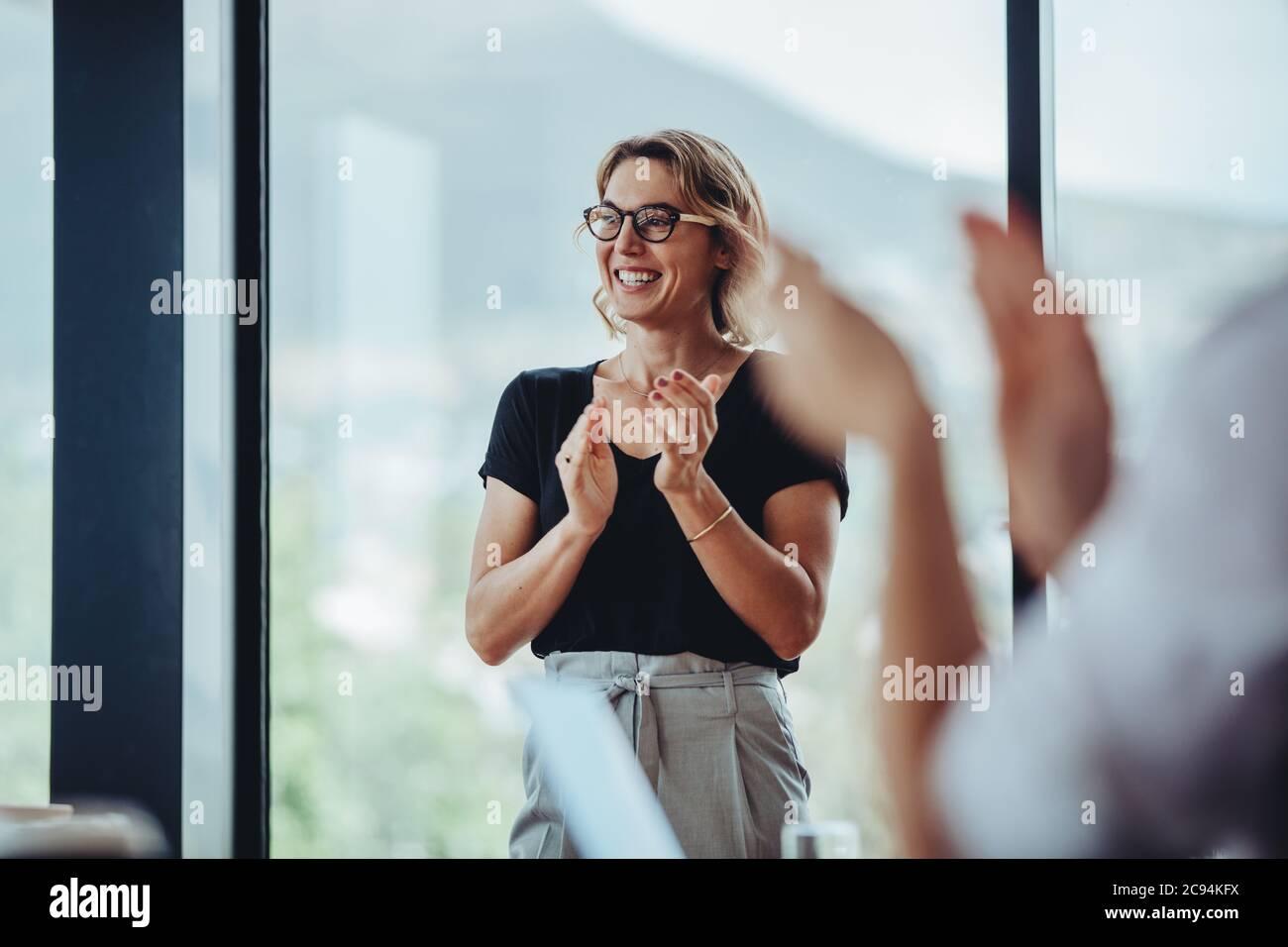 Una mujer de negocios que se alzaba las manos después de una sesión exitosa de lluvia de ideas en la sala de juntas. Gente de negocios mujeres aplaudiendo después de reunión productiva. Foto de stock