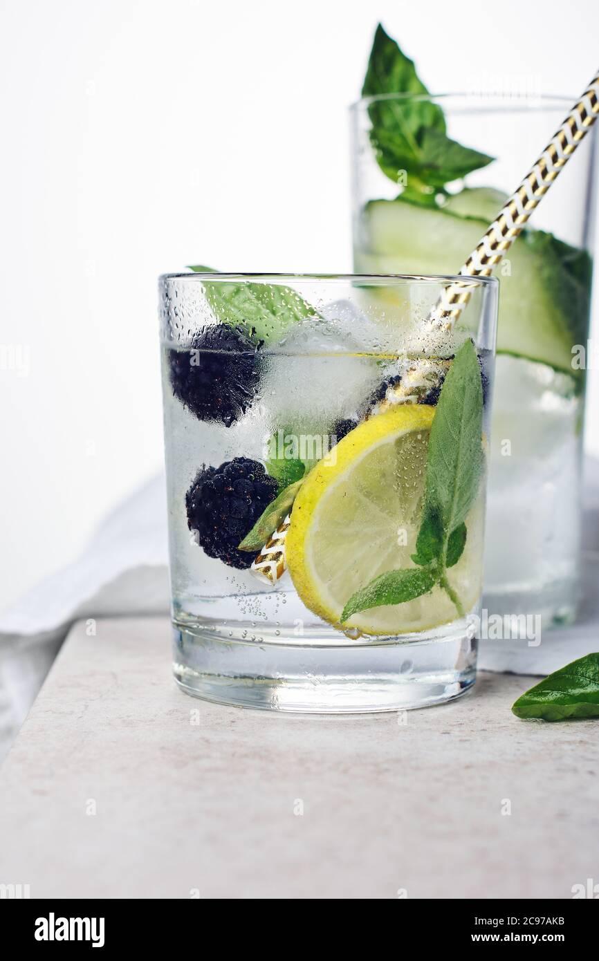 Bebida refrescante de verano, tónico con hojas de limón, mora, pepino y albahaca sobre un fondo claro. Foto de stock