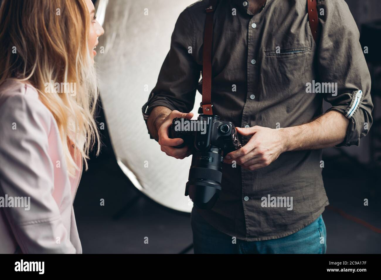hombre en busca de fotos en la cámara mientras que tiene una charla con una chica rubia, de cerca foto recortada Foto de stock