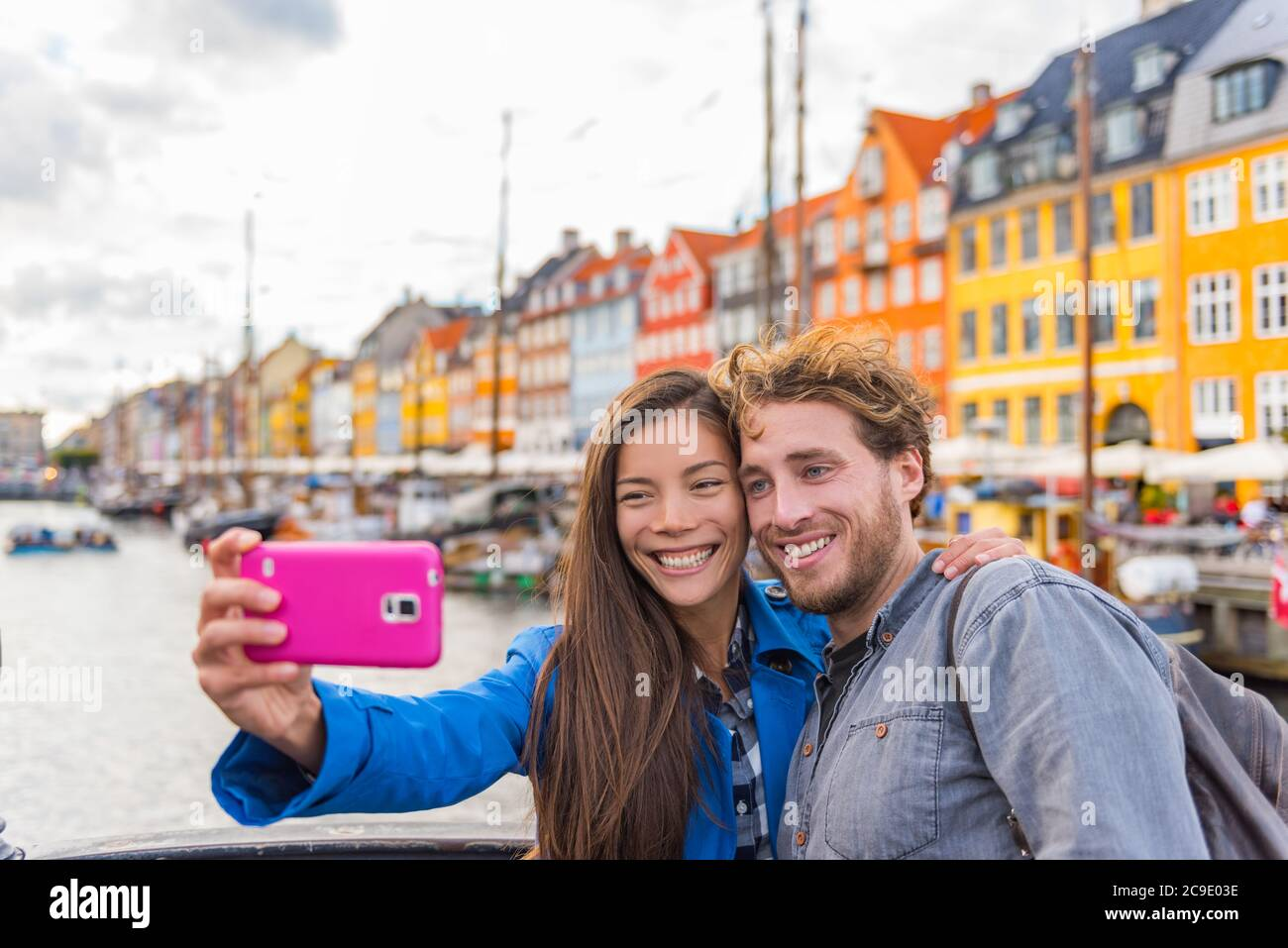 Copenhague viaje pareja turistas tomando selfie foto con cámara de teléfono. Estudiantes jóvenes sonriendo en el viejo puerto Nyhavn, el turismo danés punto de referencia en Foto de stock