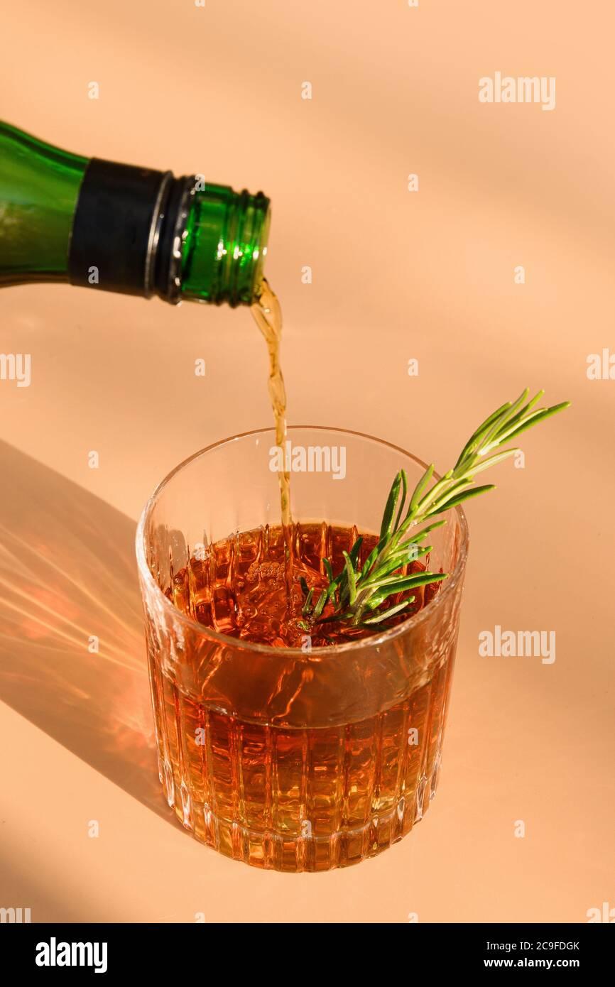 Un vaso de whisky frío adorna el romero sobre fondo beige con sombra soleada. Foto de stock