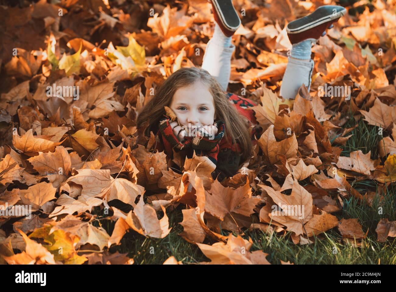 Una chica linda en el parque de otoño. Niña de hojas. Feliz niño riendo y jugando hojas en otoño al aire libre. Hermosa chica feliz que se divierte Foto de stock