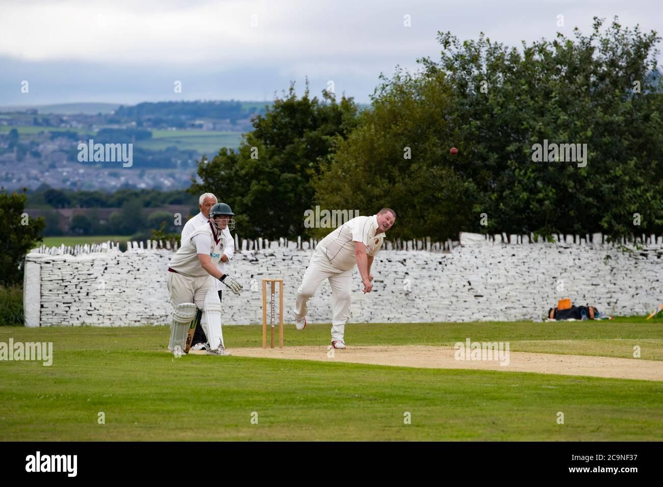 Un jugador de bolos de ritmo medio en un partido de críquet de la aldea bowling una entrega y ser observado por el árbitro y bateador no-llamativo Foto de stock