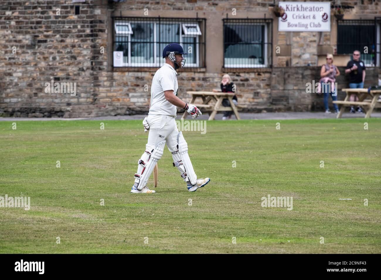 Nuevo bateador en un partido de críquet en el pueblo de West Yorkshire tomando el campo en almohadillas, guantes y casco con un palo de cricket el sábado por la tarde Foto de stock