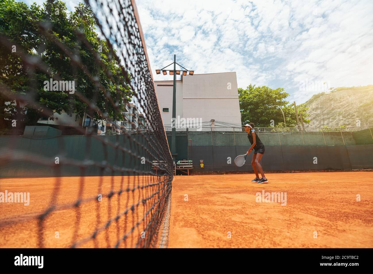 Vista de gran angular de una joven mujer biroquial delgada con una raqueta en las manos de pie sobre una superficie de cancha de arcilla y teniendo una ronda de juego de tenis o un calentamiento Foto de stock