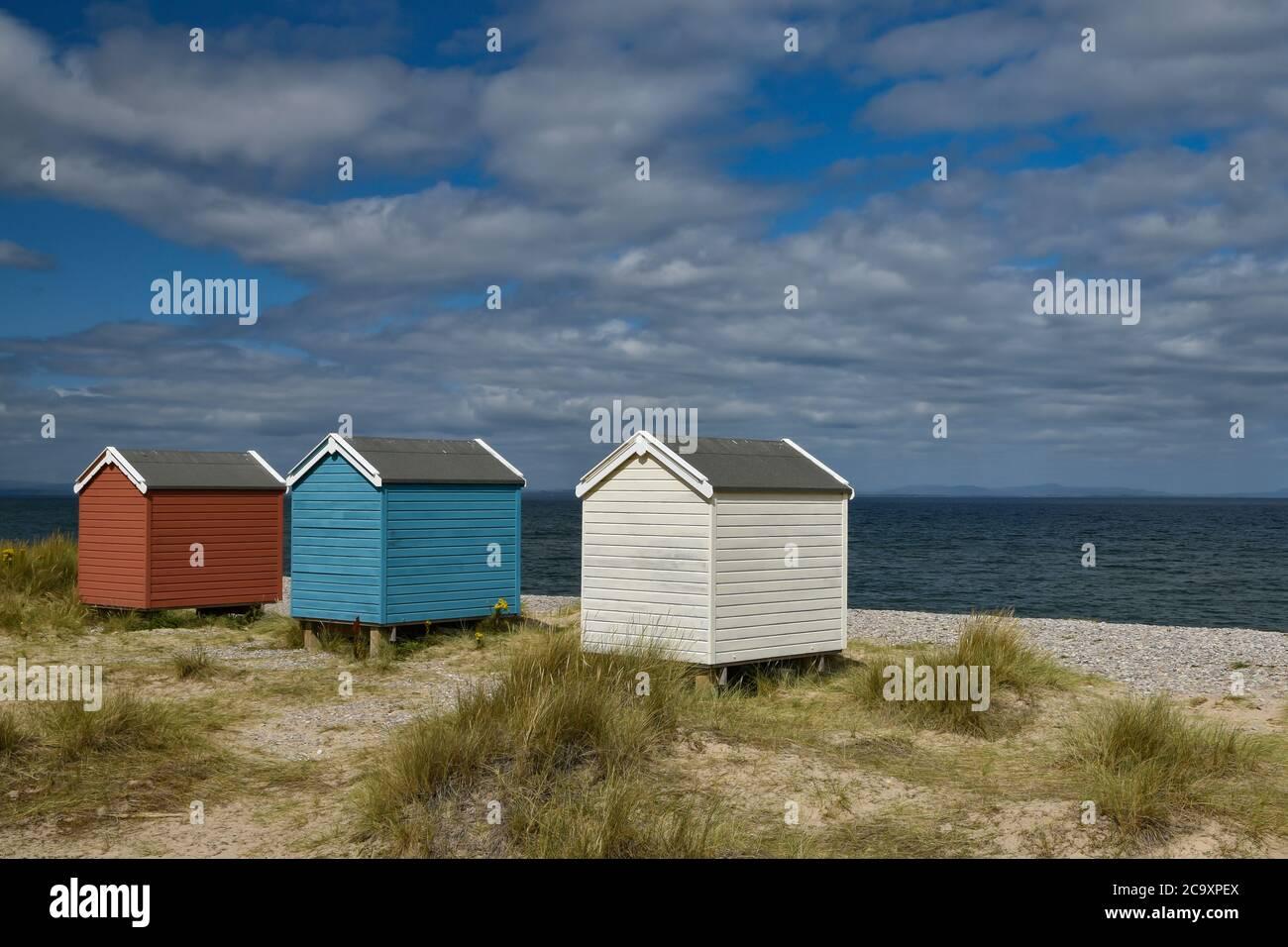 Coloridas cabañas de playa de color azul y blanco en Findhorn Beach, Moray Coast, Escocia Foto de stock