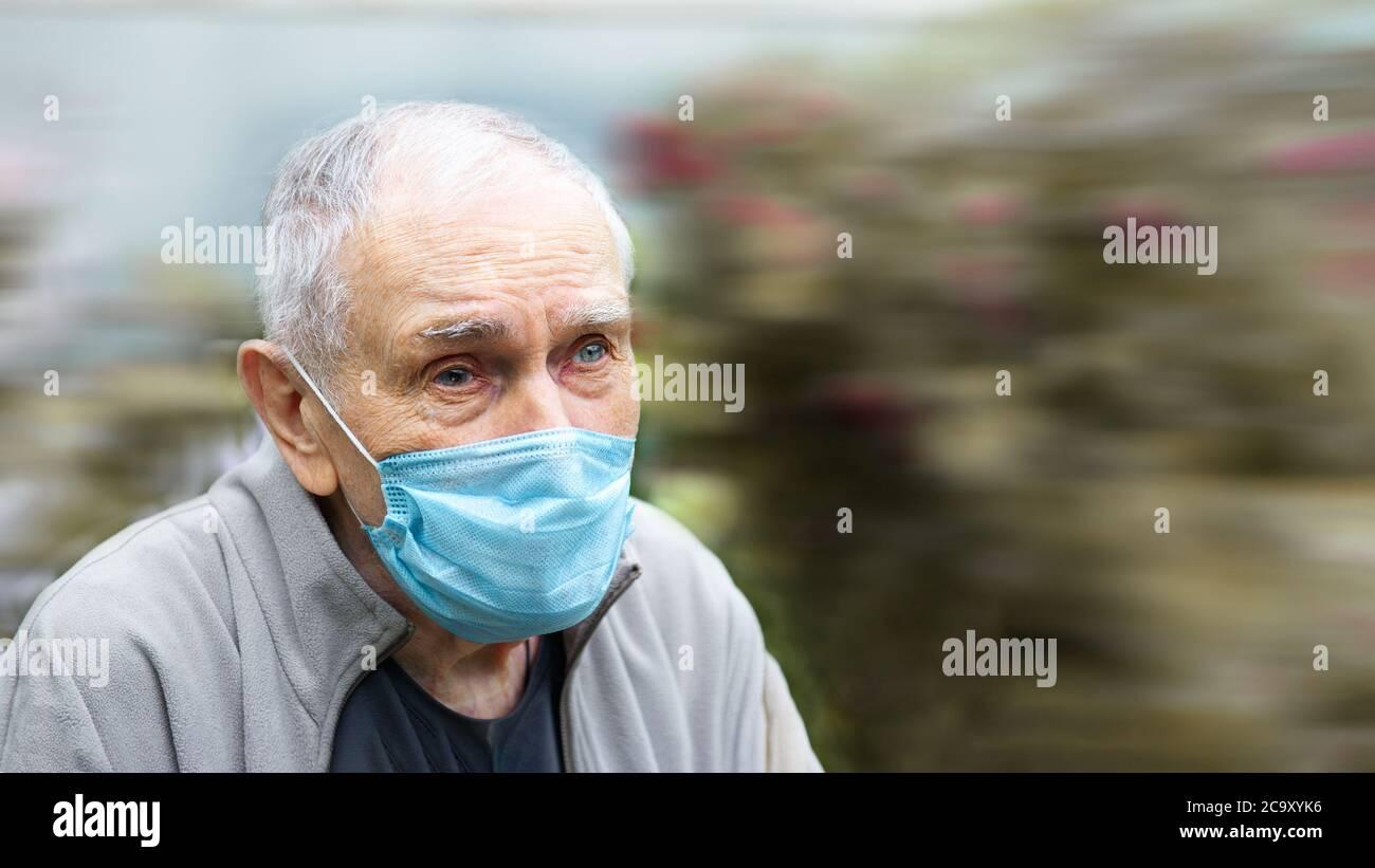 Hombre viejo en una máscara médica. Hombre viejo usa una máscara al aire libre para evitar infectarse con el virus Corvette-19. Prevención de enfermedades virales en el Foto de stock