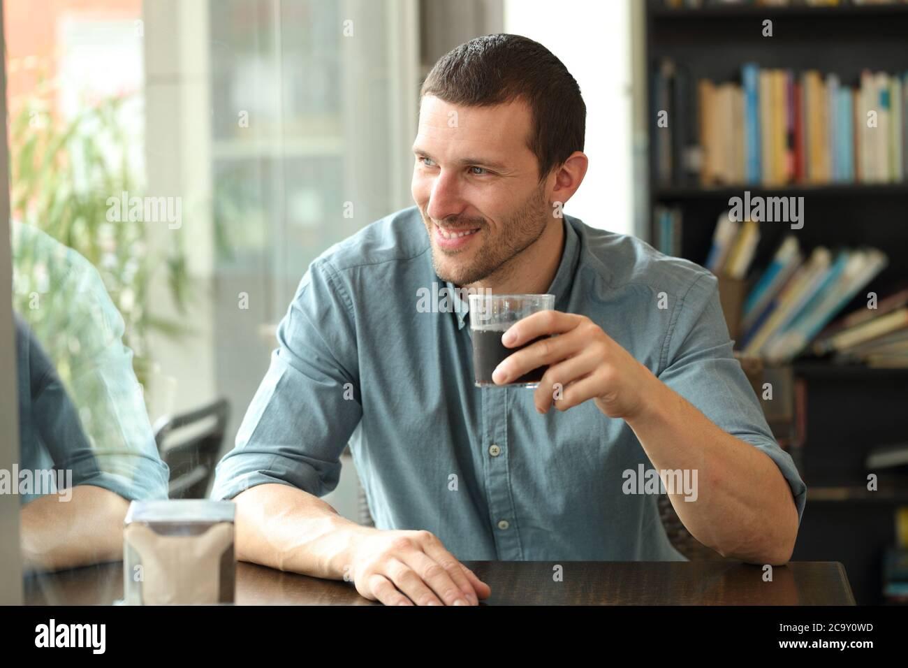 Hombre feliz mirando hacia fuera, hay una ventana sentada en una mesa de la cafetería que sostiene un vaso Foto de stock