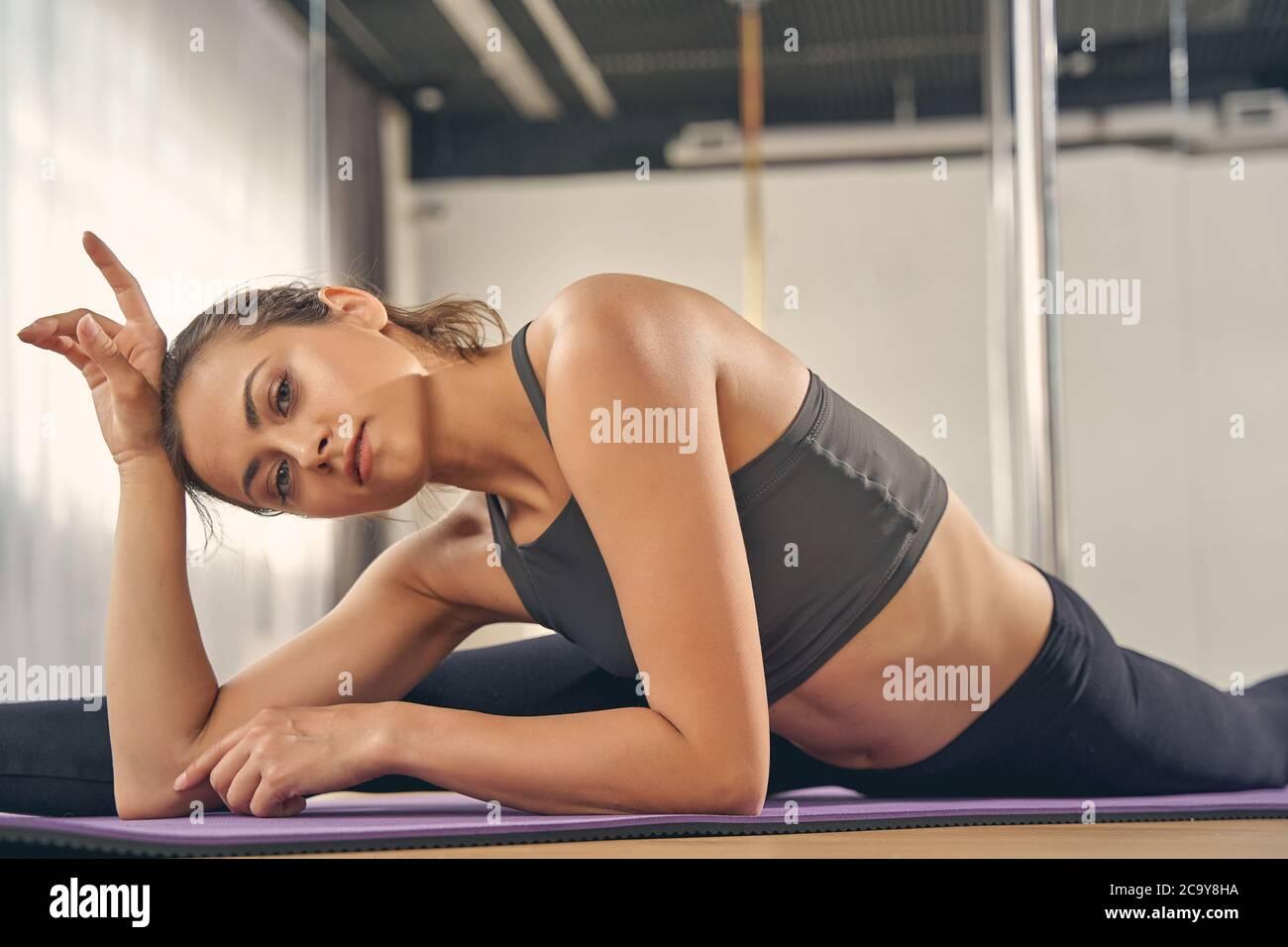 Mujer joven atractiva haciendo las divisiones en el estudio Foto de stock