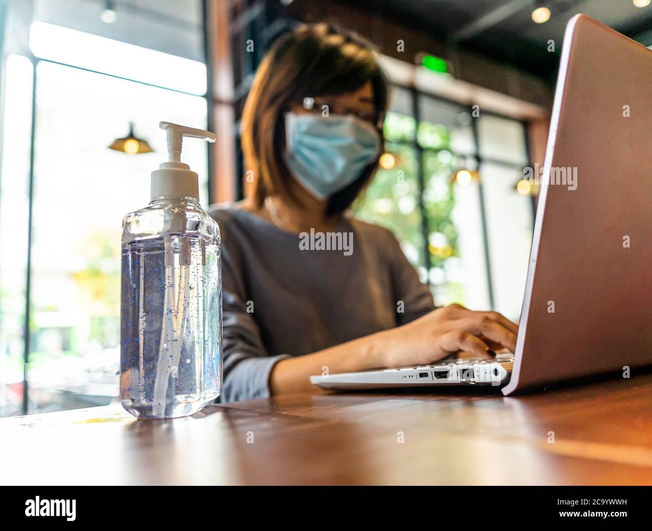 Mujer asiática joven usando computadora portátil trabajando en casa con gel de alcohol en cuarentena para coronavirus usando máscara protectora con distanciamiento social Foto de stock