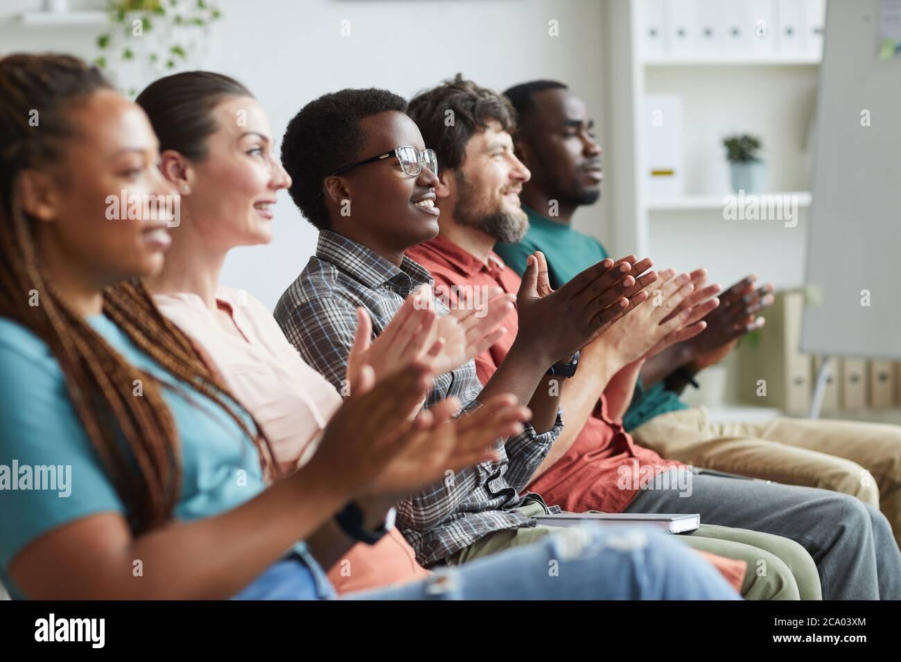 Vista lateral retrato de un grupo multiétnico de personas que aplaude mientras se sienta en fila en la audiencia o sala de conferencias, espacio para copias Foto de stock