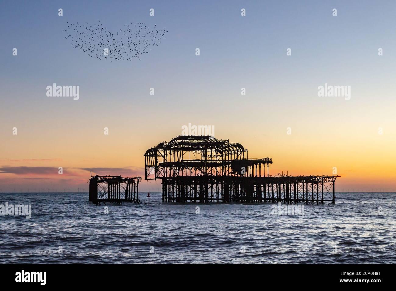 Una Murmuración en forma de corazón de los Starlings sobre el Old West Pier de Brighton, al atardecer Foto de stock