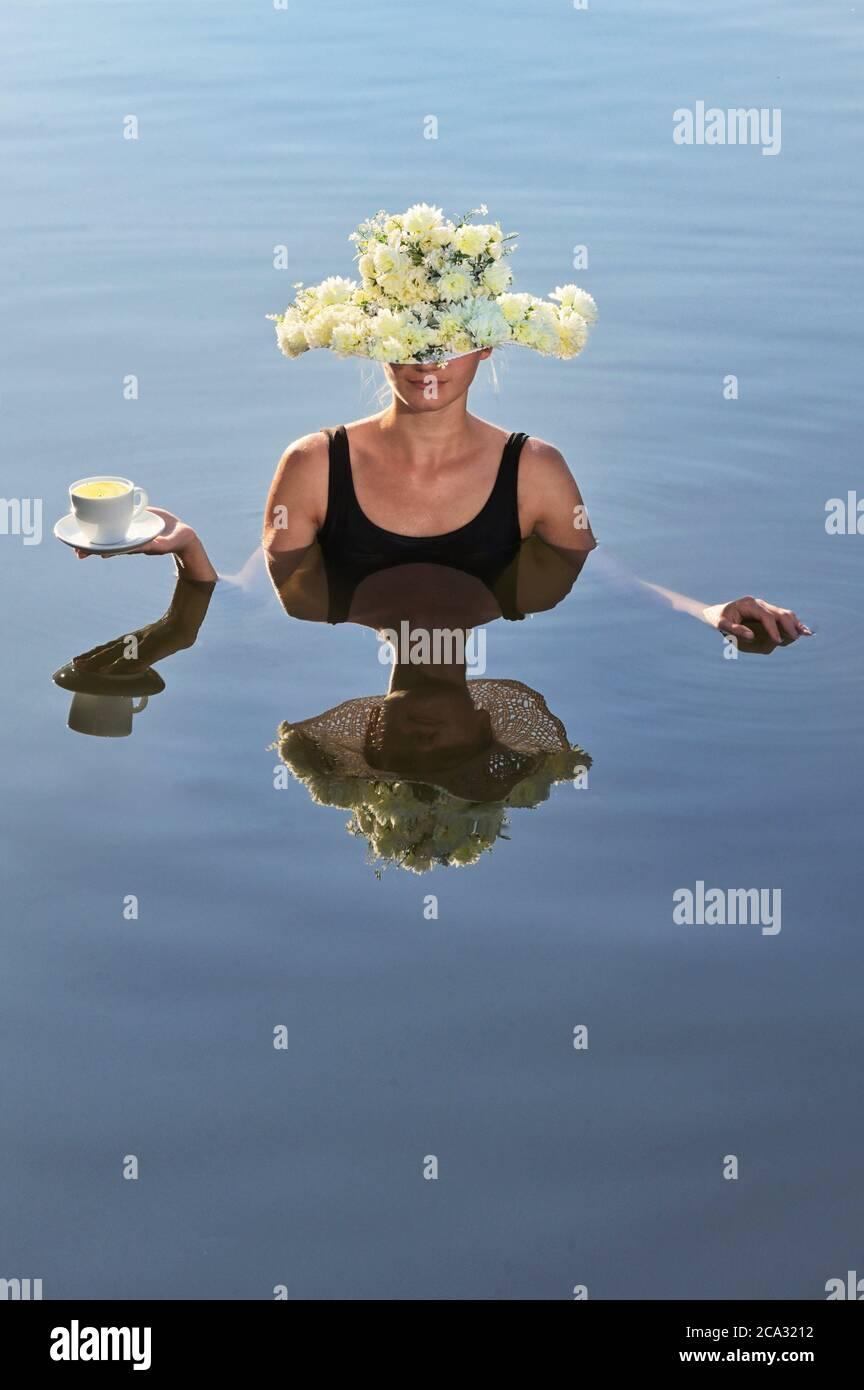Mujer joven con sombrero de flores sirviendo una taza de café. Foto de stock