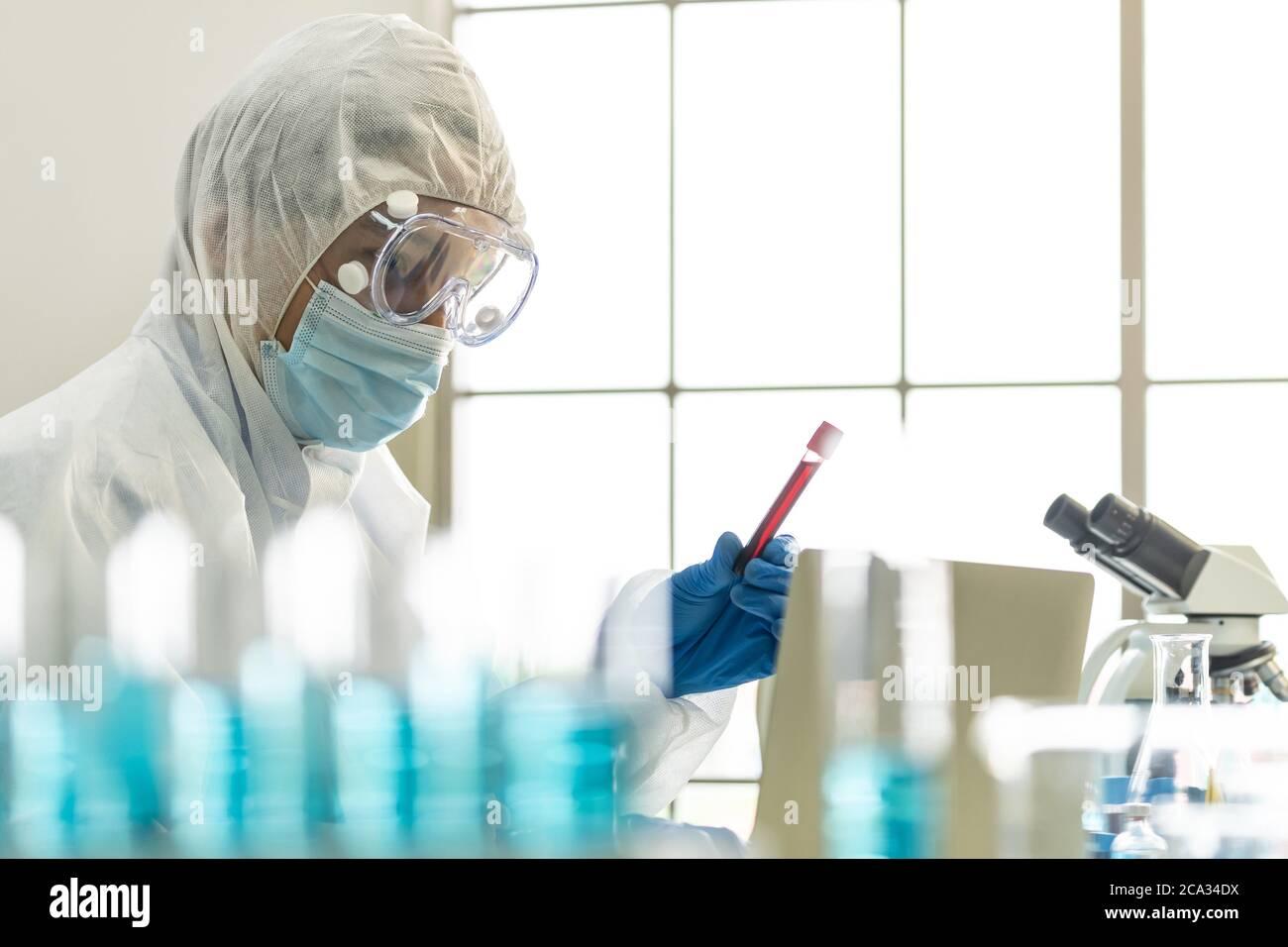 Los científicos sostienen un tubo de análisis de muestras de sangre y examinan su investigación y desarrollan una vacuna contra la pandemia de coronavirus covid-19. Tecnología de Ciencias Médicas Foto de stock