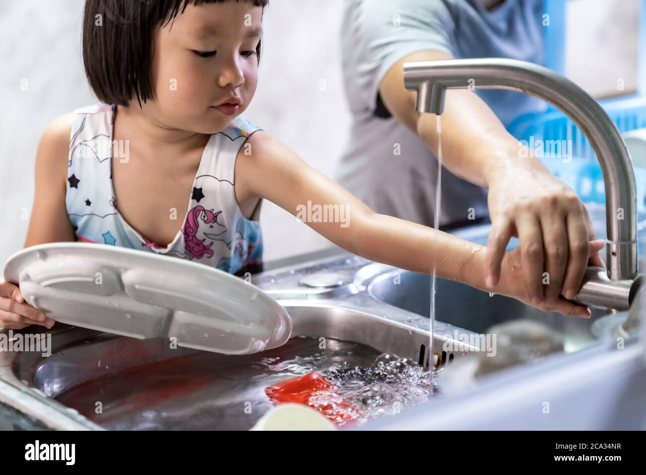 Niña asiática lavando plato y vajilla con su mamá, las tareas domésticas para el niño hacen la función ejecutiva para el niño. Trabajo en casa para niños estilo de vida y familia Foto de stock