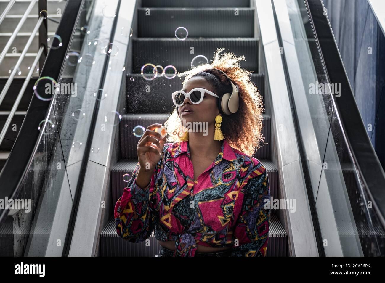 Dama afroamericana en gafas de sol y blusa de colores sentada en escalera en movimiento con boca abierta mientras soplaba burbujas en la parte de atrás iluminada. Foto de stock