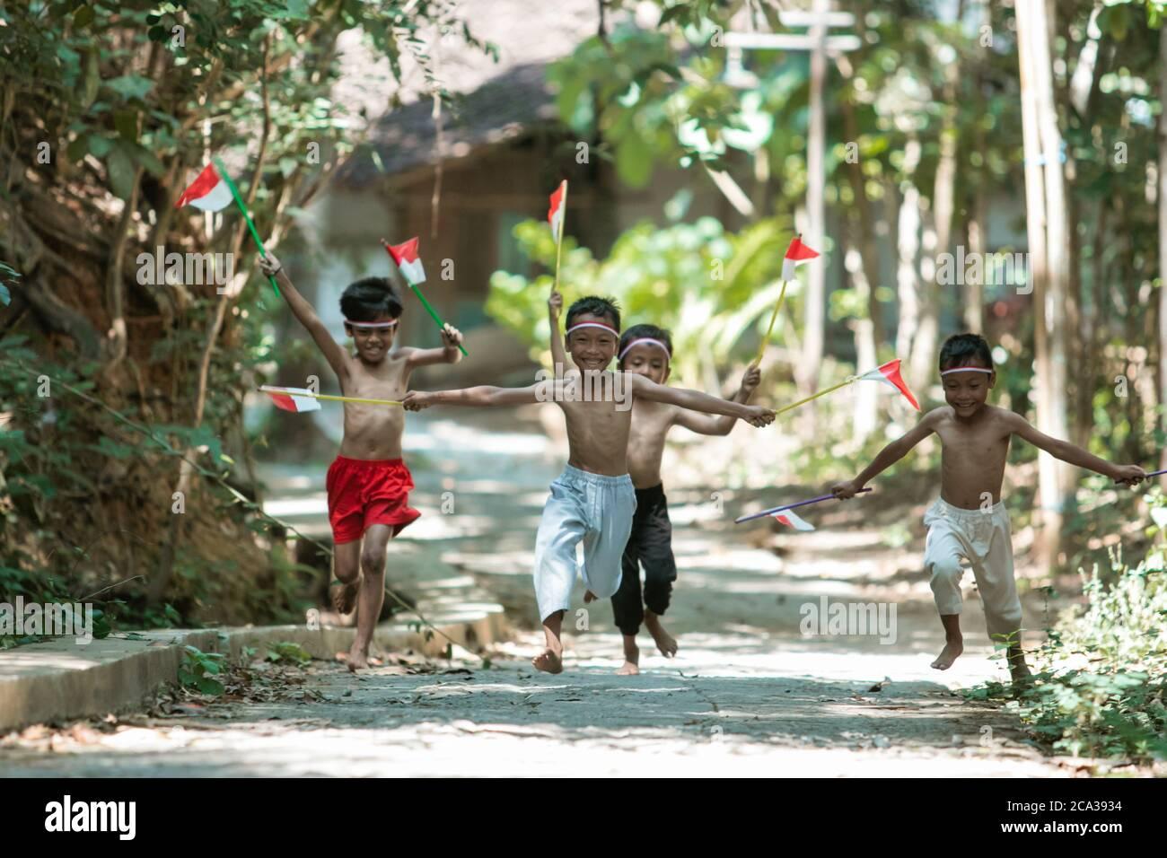 tener un grupo divertido de niños corriendo sin ropa persiguiendo a cada uno otros cuando se mantiene pequeña la bandera roja y blanca y. se levantó la bandera contra un fondo de árbol Foto de stock
