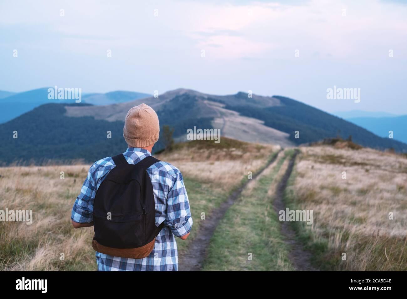 Hombre con mochila en montañas road. Concepto de viaje. Fotografía paisajística Foto de stock