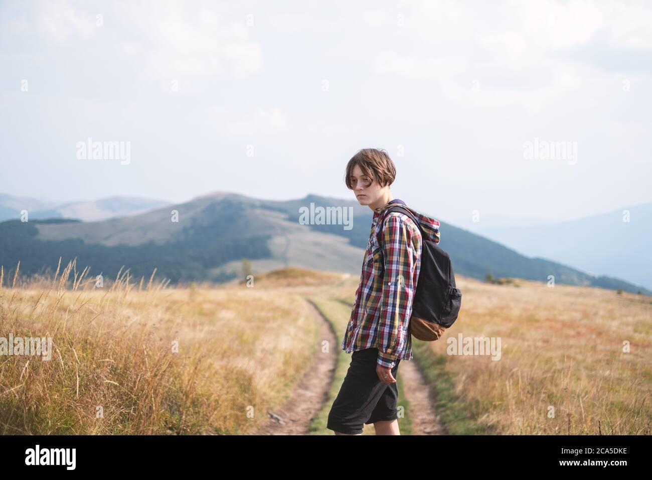 Niño con mochila en carretera de montaña. Concepto de viaje. Fotografía de paisajes Foto de stock