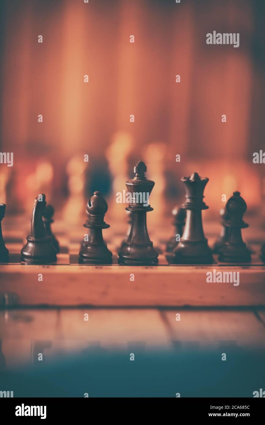 Juego de Ajedrez. Tablero de ajedrez con figuras en él en la suave luz de la habitación caliente. Deportes intelectuales. Foto de stock