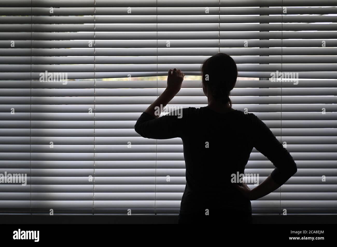 Mujer adulta sospechosa mirando fuera de la ventana de la casa desde detrás de las cortinas venecianas. Foto conceptual de la persona que tiene Pistanthrofobia y Agorafobia, Foto de stock