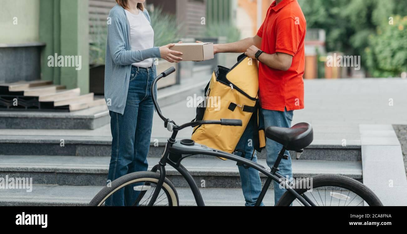 Shopaholic y entrega en línea. Mensajero de bicicletas con mochila y bicicleta da caja de cartón al cliente Foto de stock