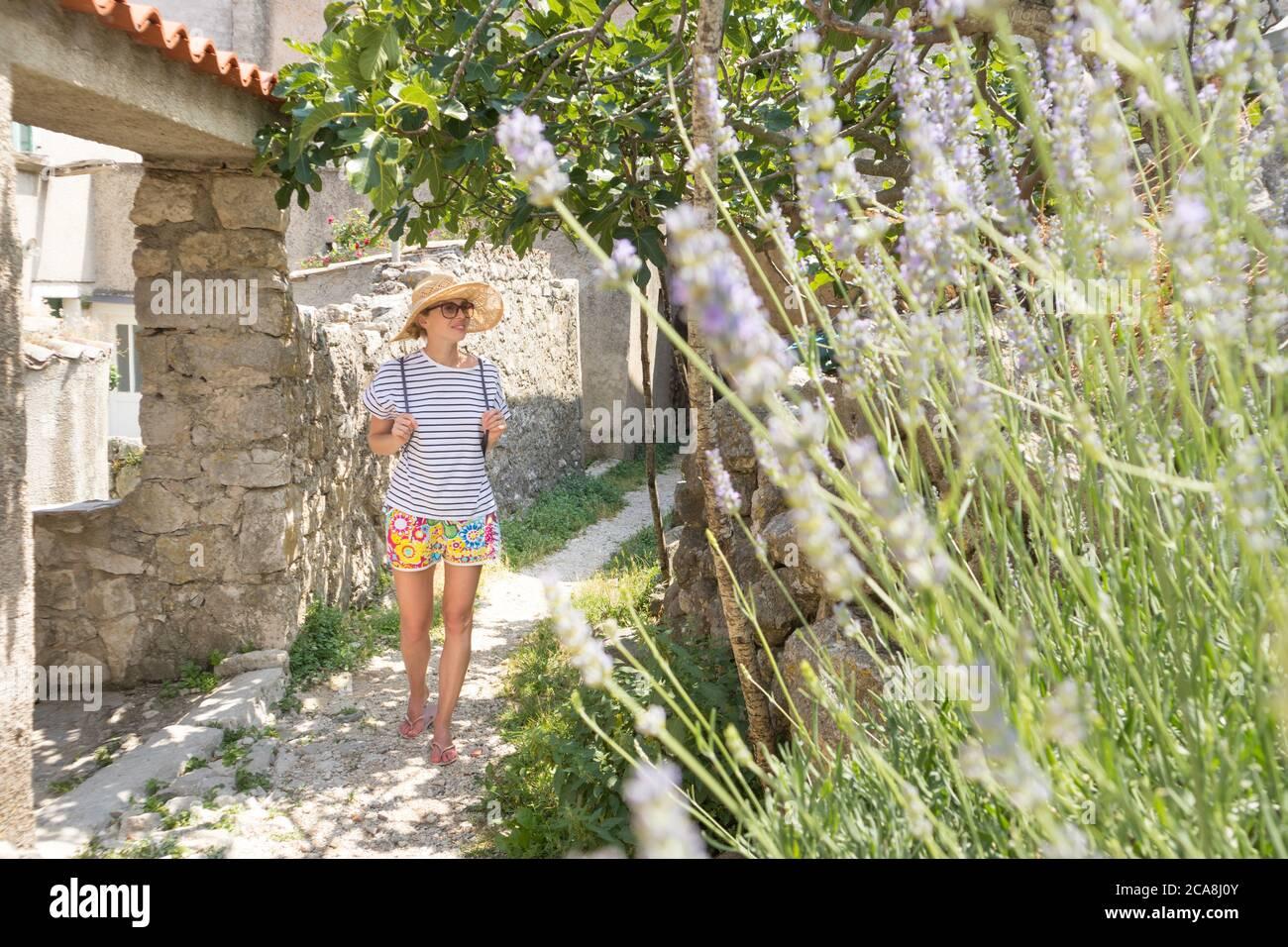 Vista trasera de la hermosa rubia joven viajero con sombrero de paja de turismo y disfrutar de las vacaciones de verano en una antigua ciudad costera tradicional Foto de stock