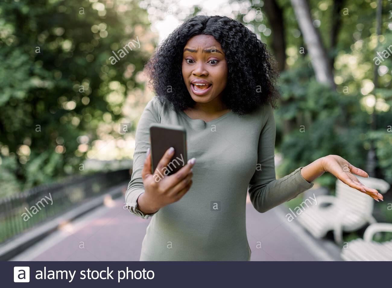 Retrato de una joven disidente sorprendido asustada mujer africana curly leyendo mensaje de texto en el teléfono móvil, mientras que caminar al aire libre en verano hermoso Foto de stock