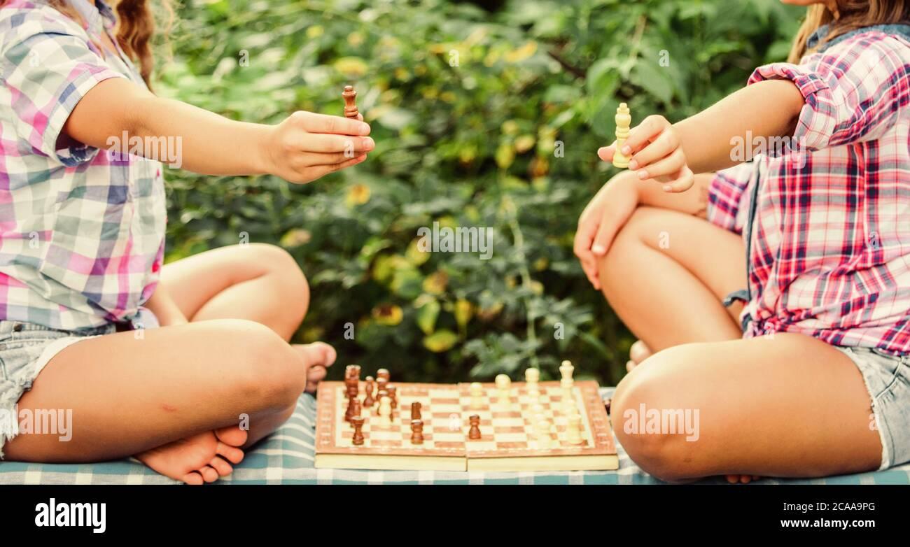 Jugar al ajedrez. Hermanas jugando al ajedrez. Los niños juegan al ajedrez al aire libre la naturaleza de fondo. Concepto de deporte y pasatiempo. El concepto de estrategia. El desarrollo cognitivo. Juego intelectual. La toma de decisiones. Los niños inteligentes. Foto de stock