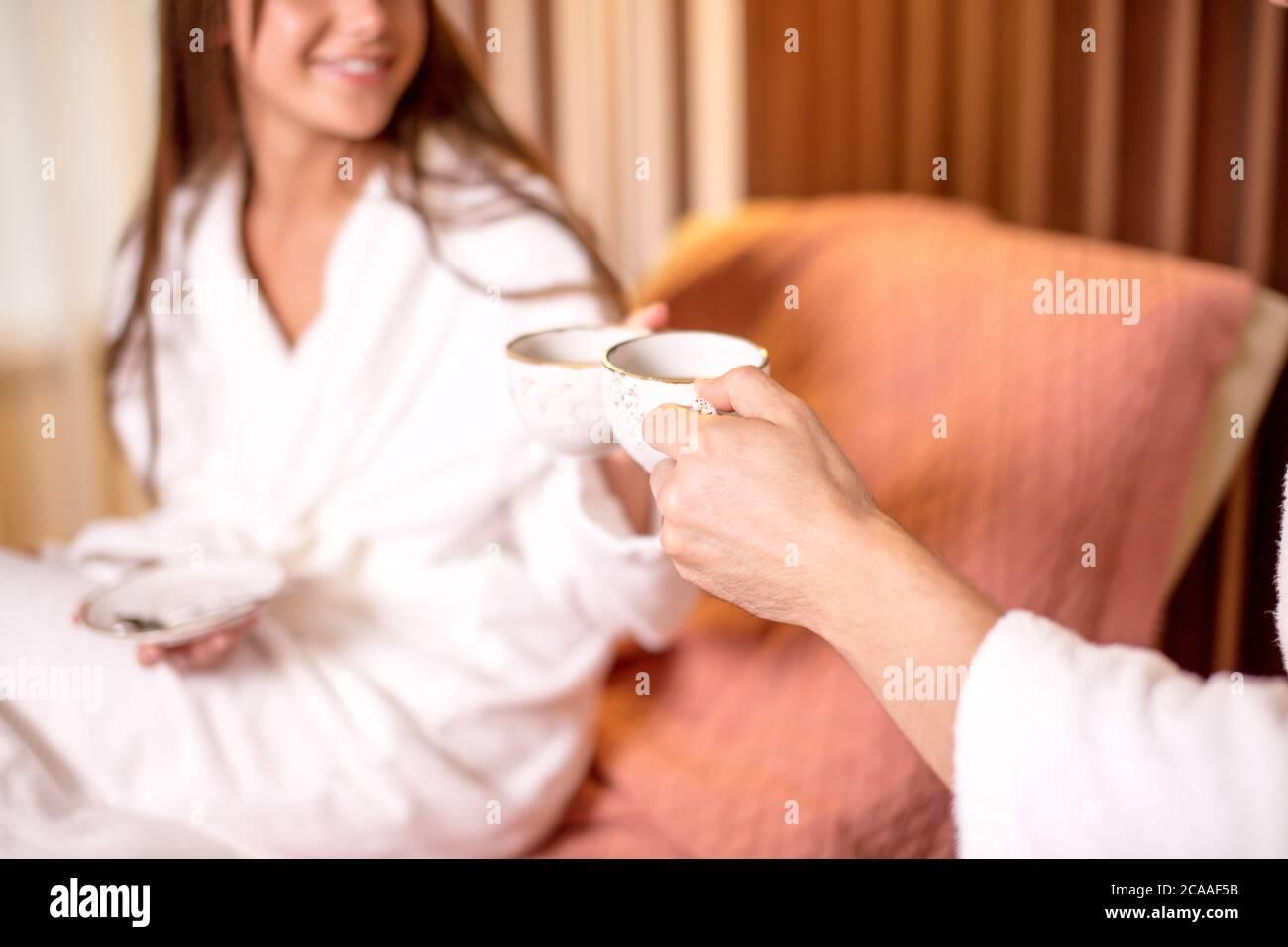 una pareja joven que se alaba de un ambiente de miel en la habitación del hotel. foto de primer plano vista lateral. café matutino para gente amante Foto de stock