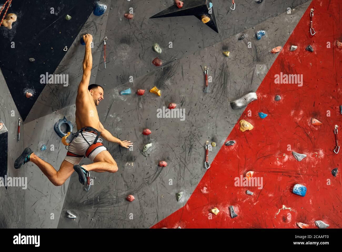 Escalador macho instructor escaladas en pared artificial pintado en colores rojo y gris en el interior. Un estilo de vida activo y trepar rocas concepto. Foto de stock