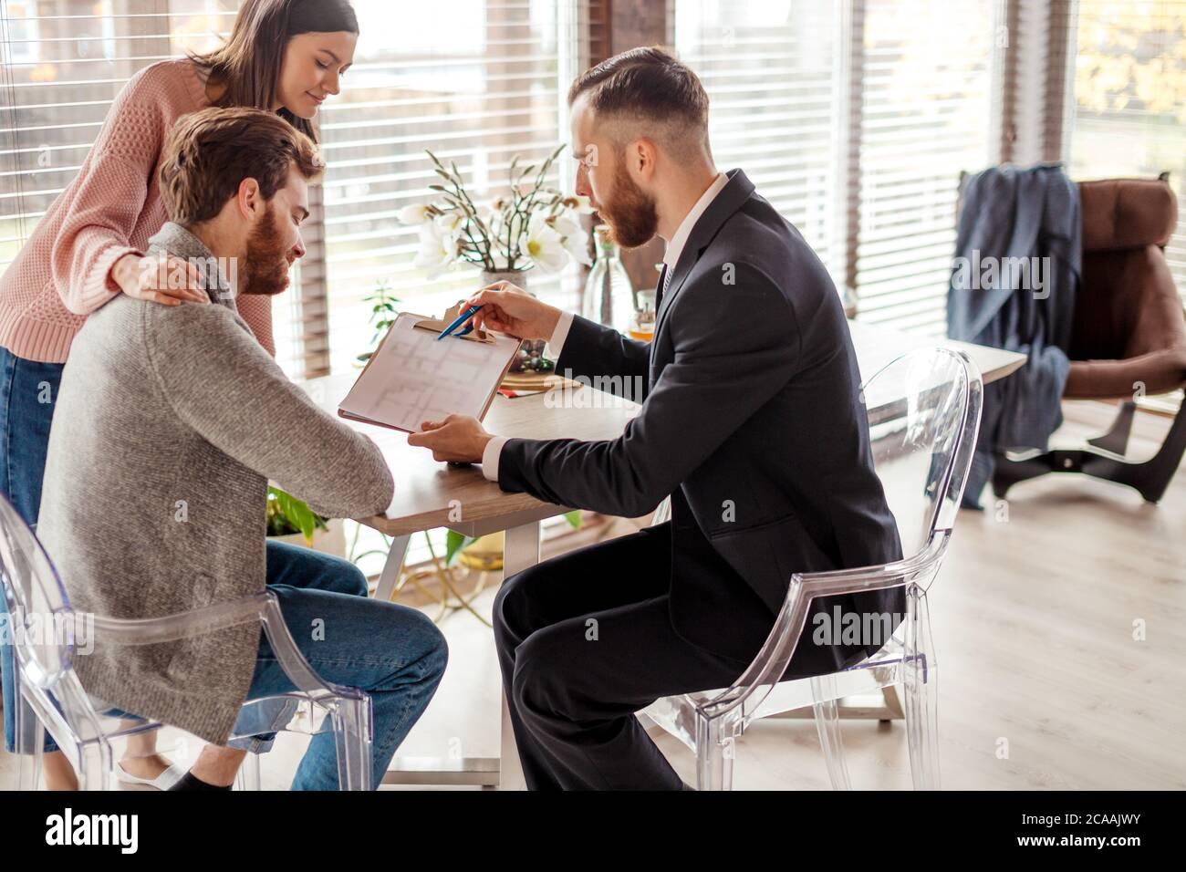 Caucasian respetable pareja de compra de apartamento, los compradores de bienes raíces listo para concluir un acuerdo con el agente de bienes raíces después de firmar documentos para Realt Foto de stock