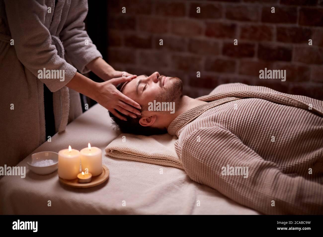 Salón de belleza, concepto de tratamiento. El joven caucásico recibe un masaje en la cabeza y la cara tumbado en el escritorio con los ojos cerrados, calma Foto de stock