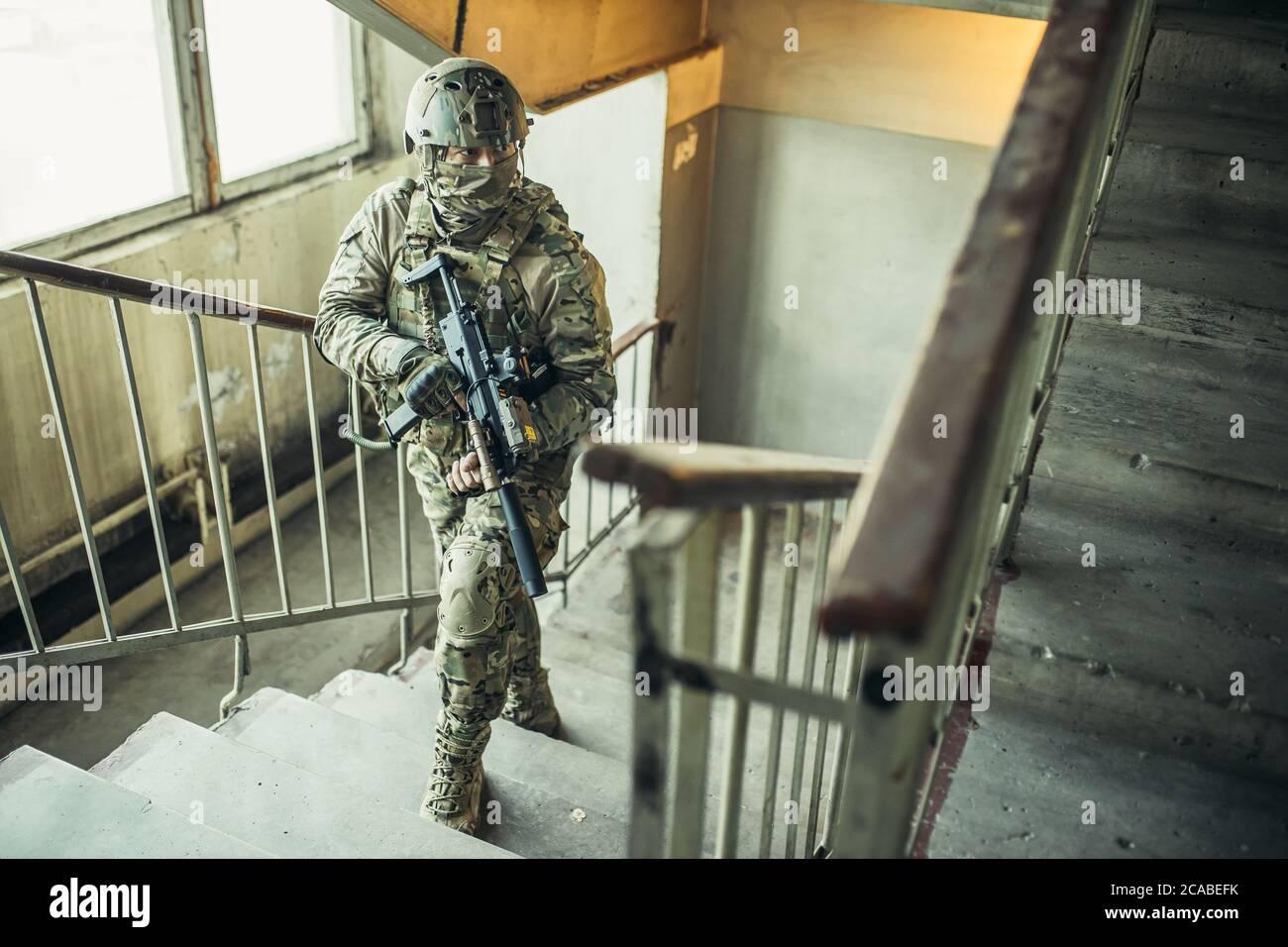 el concepto del ejército. soldado con arma en el aterrizaje, subiendo las escaleras, buscando enemigo para disparar, proteger. Foto de stock
