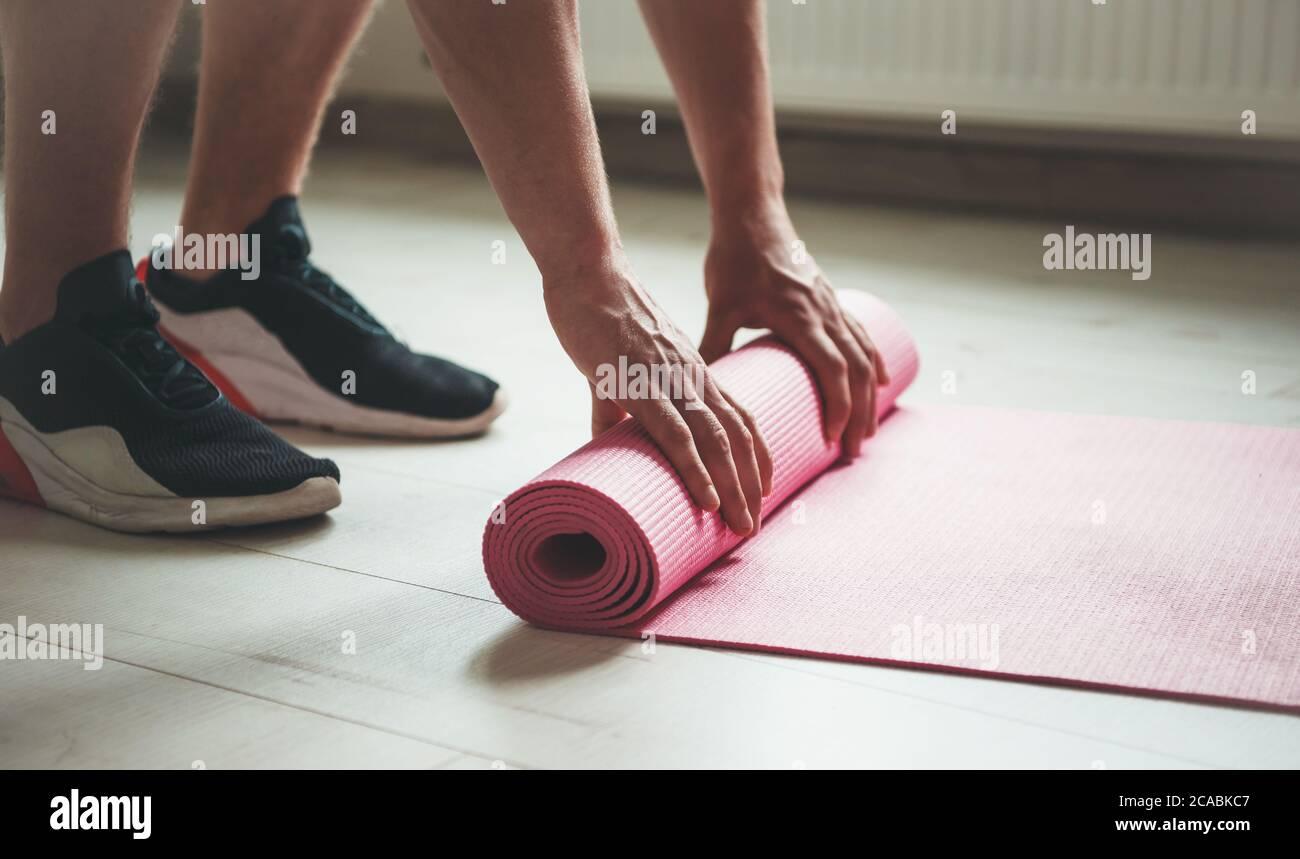 Vista lateral foto de una persona caucásica en sportswear terminando su procedimiento de yoga y recogiendo la alfombra Foto de stock
